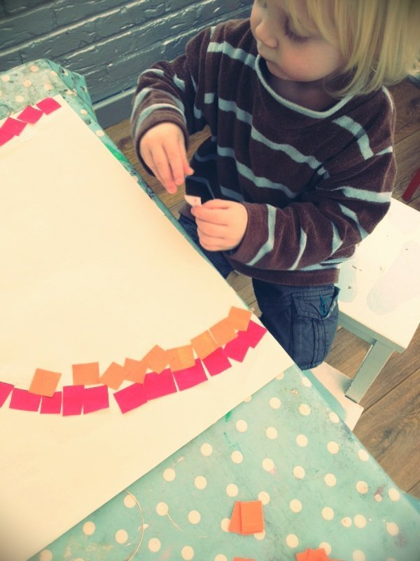 toddler sticking mosaic squares onto white paper to create a mosaic kids rainbow craft