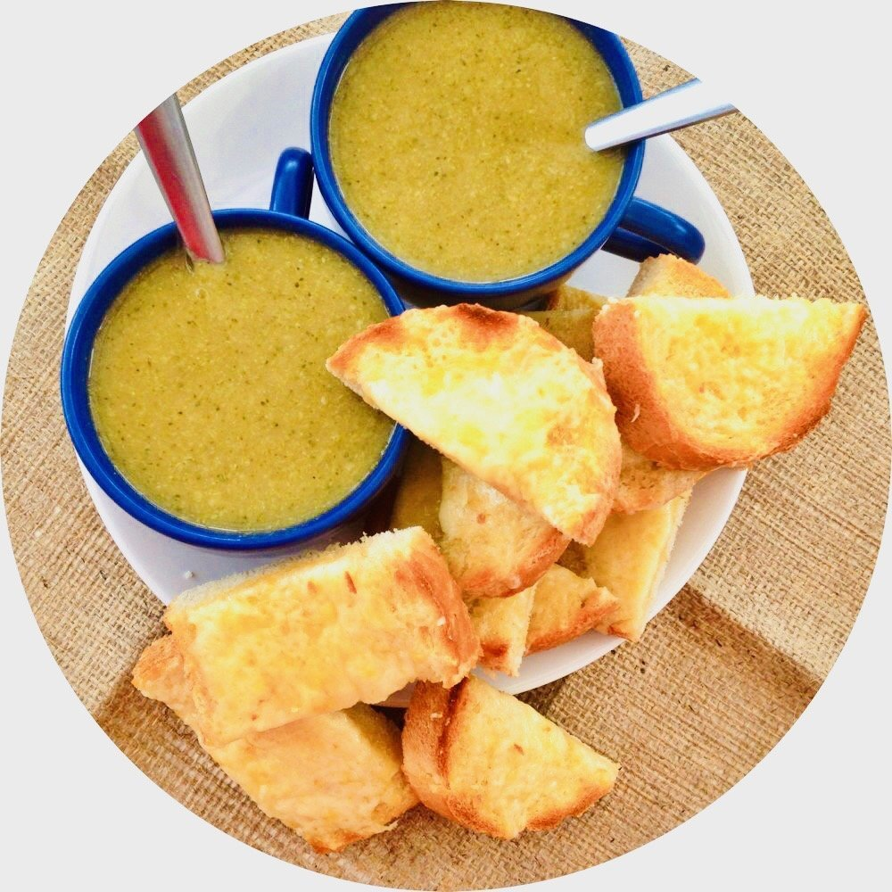 broccoli soup with marmite served in blue bowls alongside a pile of grilled cheese sandwiches
