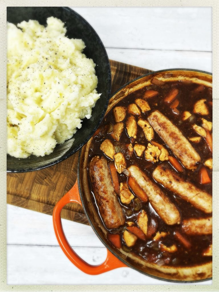 chicken and sausage casserole in an enamel casserole pan served alongside a bowlful of creamy mashed potatoes