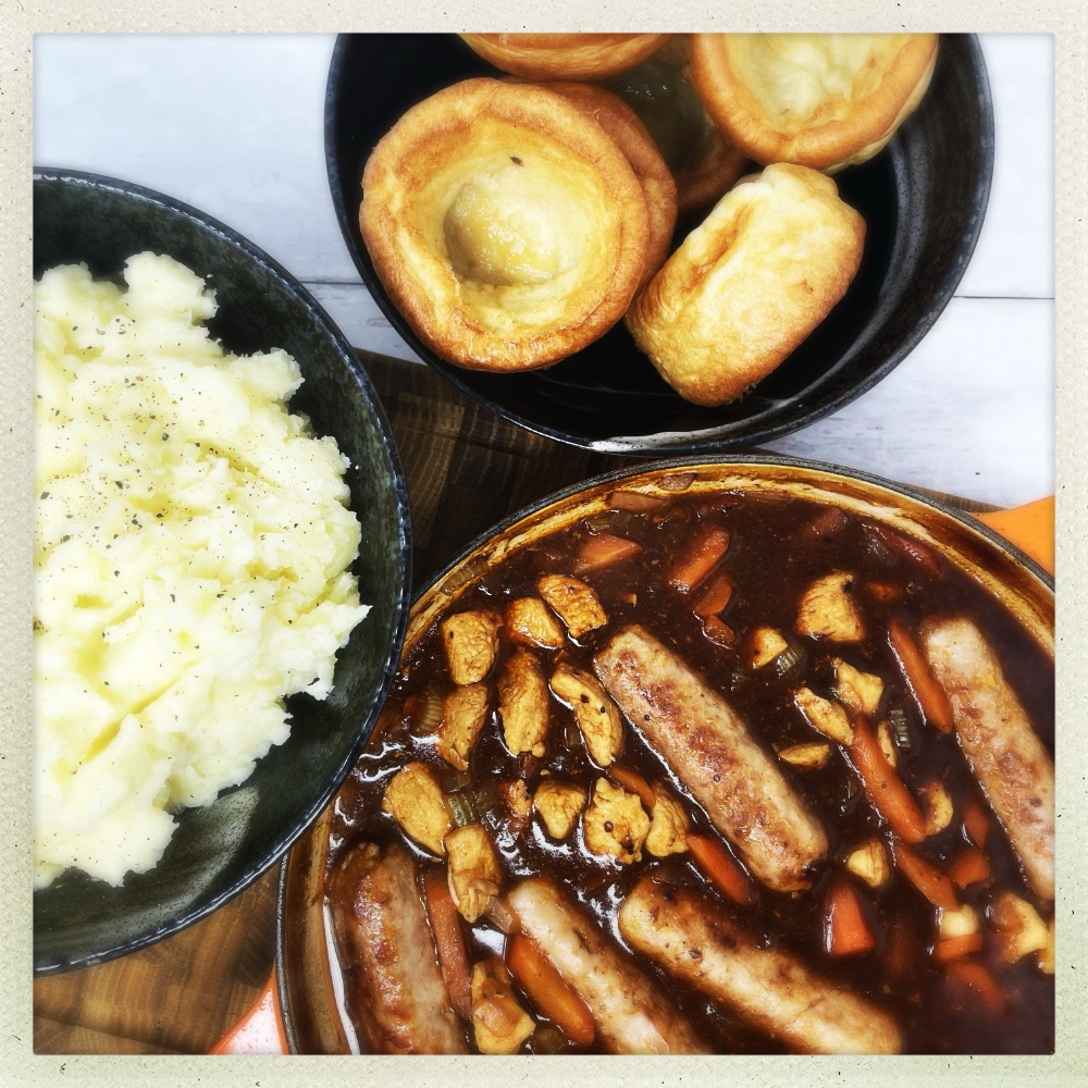 chicken and sausage casserole in an enamel casserole pan served alongside a bowlful of creamy mashed potatoes and bowl of Yorkshire puddings