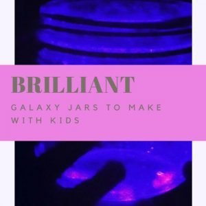 glass kilner jar being used as a galaxy jar glowing blue and pink with shadowy hands holding the jar. Text overlay saying 'Brilliant galaxy jars to make with kids'