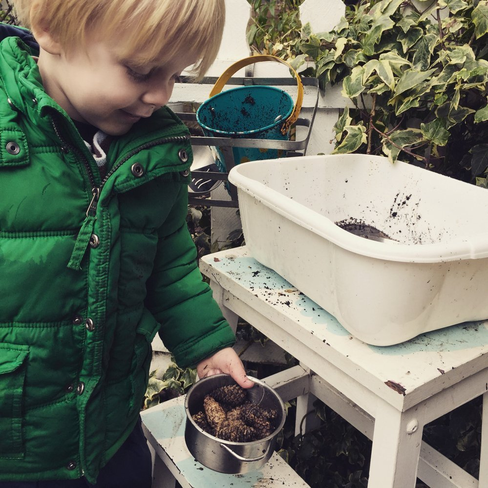 diy mud pie kitchen in the garden made with repurposed household items - small boy playing with mud, pine cones and water