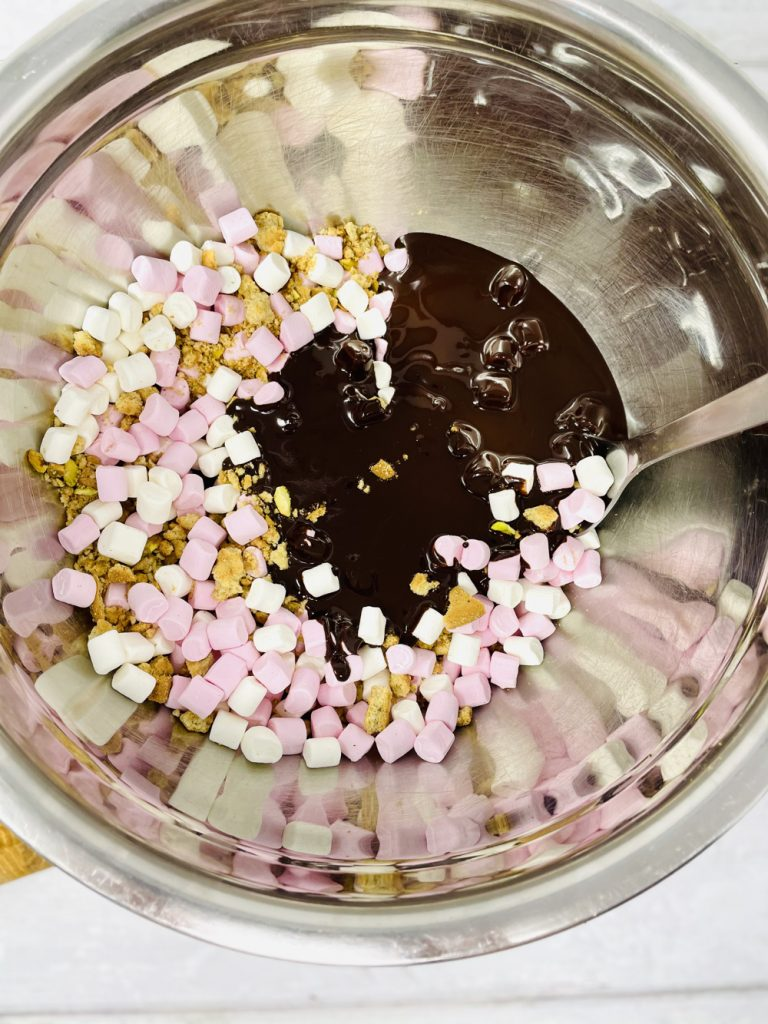 melted chocolate poured into a bowl of smashed digestive biscuits, pistachio nuts and pink and white marshmallows ready to mix into rocky roads