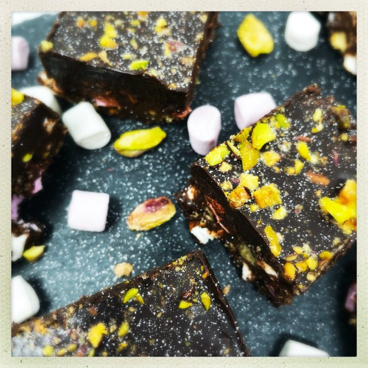 pistachio rocky road bars sprinkled with pistachios and edible glitter served on a black slate