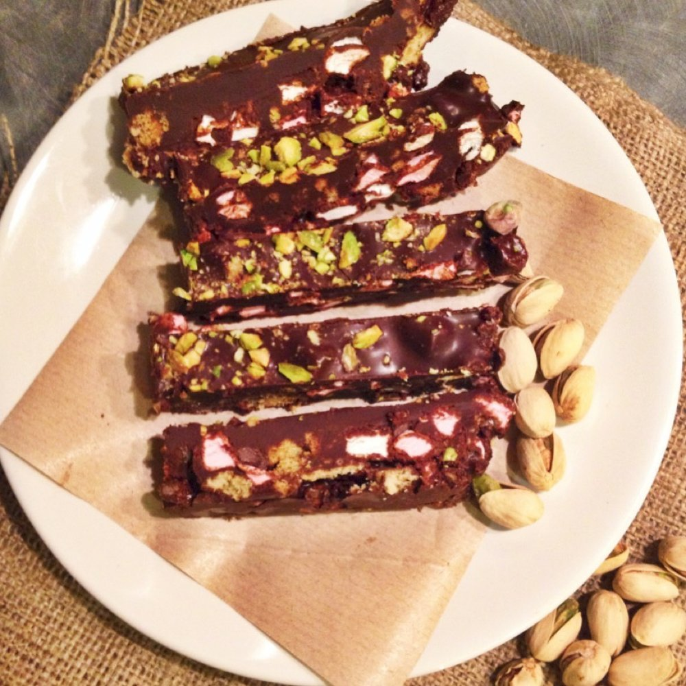 homemade pistachio rocky road bars on a white plate with brown paper