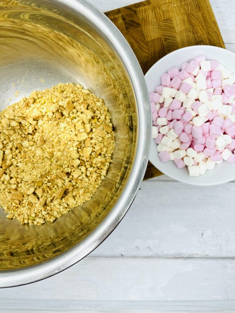 bowl of smashed up digestive biscuits and pink and white marshmallows ready to make into rocky roads