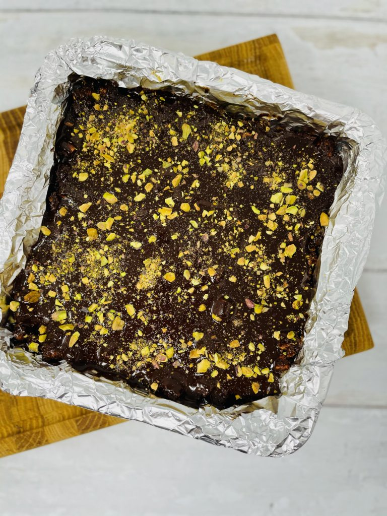 rocky road coated in chocolate and sprinkled with pistachios and glitter ready to set in the fridge