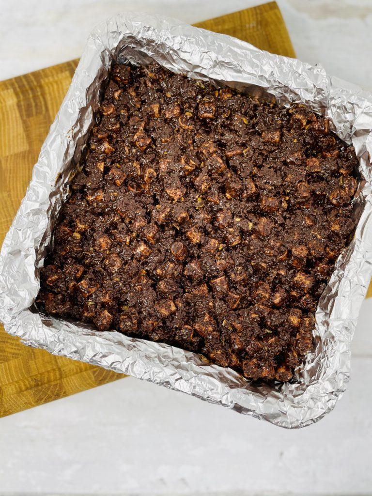 rocky road mixture packed into a foil lined baking tin