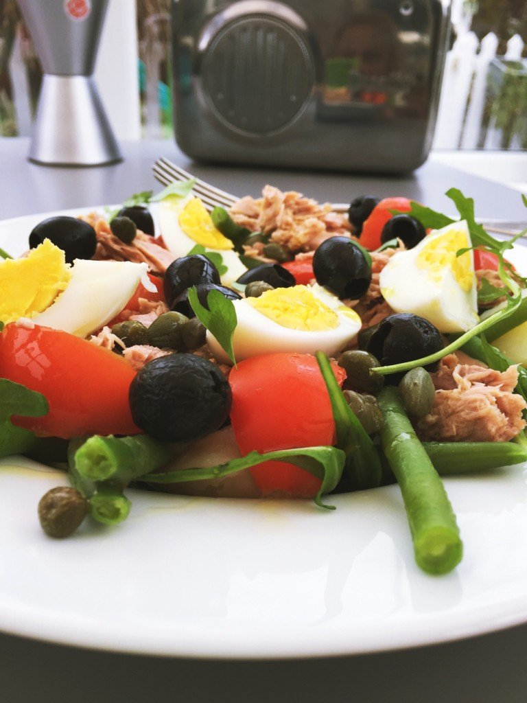 plate of tuna nicoise, green beans, rocket, boiled eggs, capers, tuna, and black olives