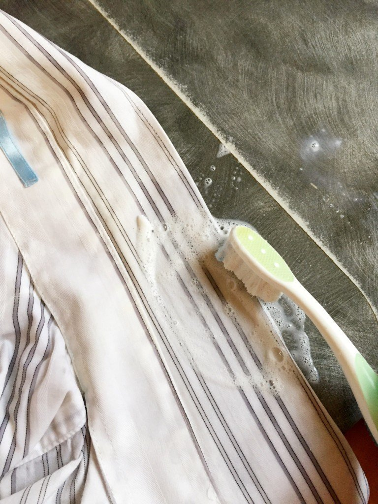 grey and white striped shirt with ink stain damped being rubbed with soapy water and brushed with a toothbrush