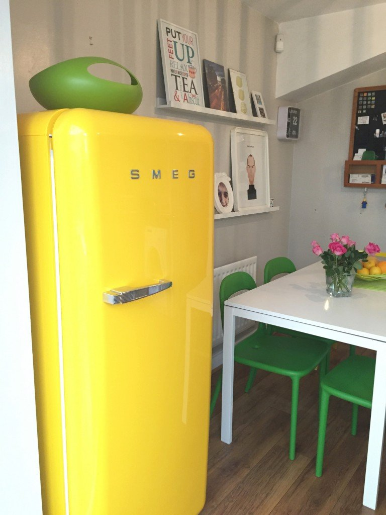 yellow smeg fridge with green Joesph Joseph salad bowl on top - white kitchen table in the background with green chairs