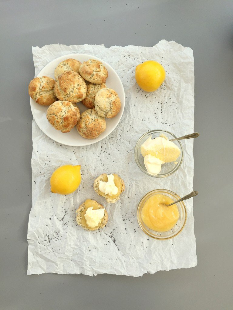 white plate piled high with lemon and poppy seed scones, on white paper alongside the scones are lemons, a put of clotted cream and pot of lemon curd - with one scone cut open and spread with lemon curd and clotted cream ready to be eaten