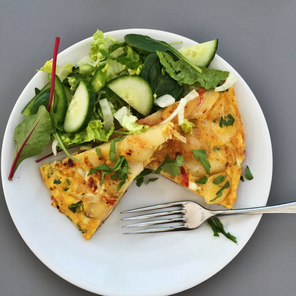 white plate with two wedges of spanish omelette and a large green side salad