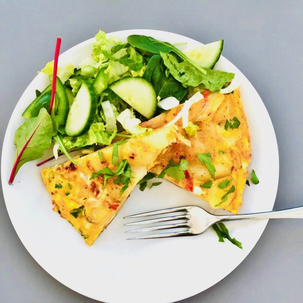 spanish omelette with onions and peppers served in wedges on a white plate with a fresh green salad on the side