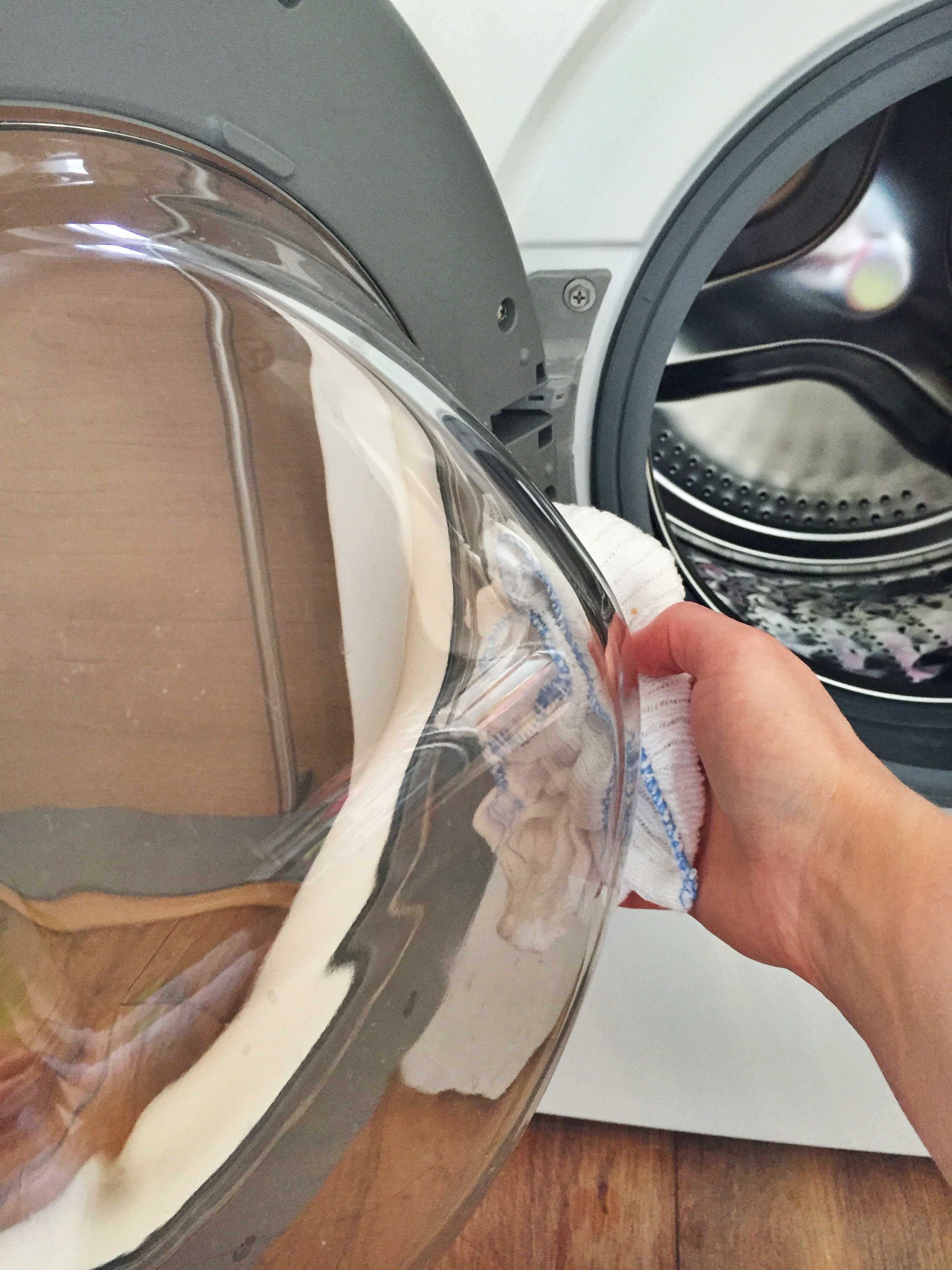 glass door on a samsung washing machine being wiped with a soft white cloth to clean it