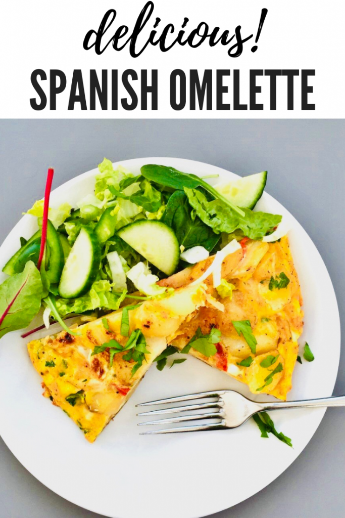 "spanish omelette with onions and peppers served in wedges on a white plate with a fresh green salad on the side. Text overlay ""delicious spanish omelette"""