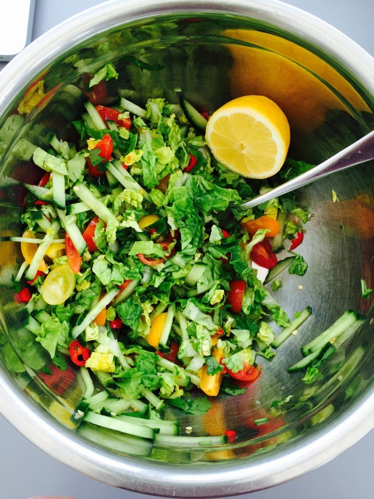 bowl full of Indian style salad with fresh lettuce, cucumber, tomatoes, herbs and freshly sliced chillies served with lemon wedges for squeezing over