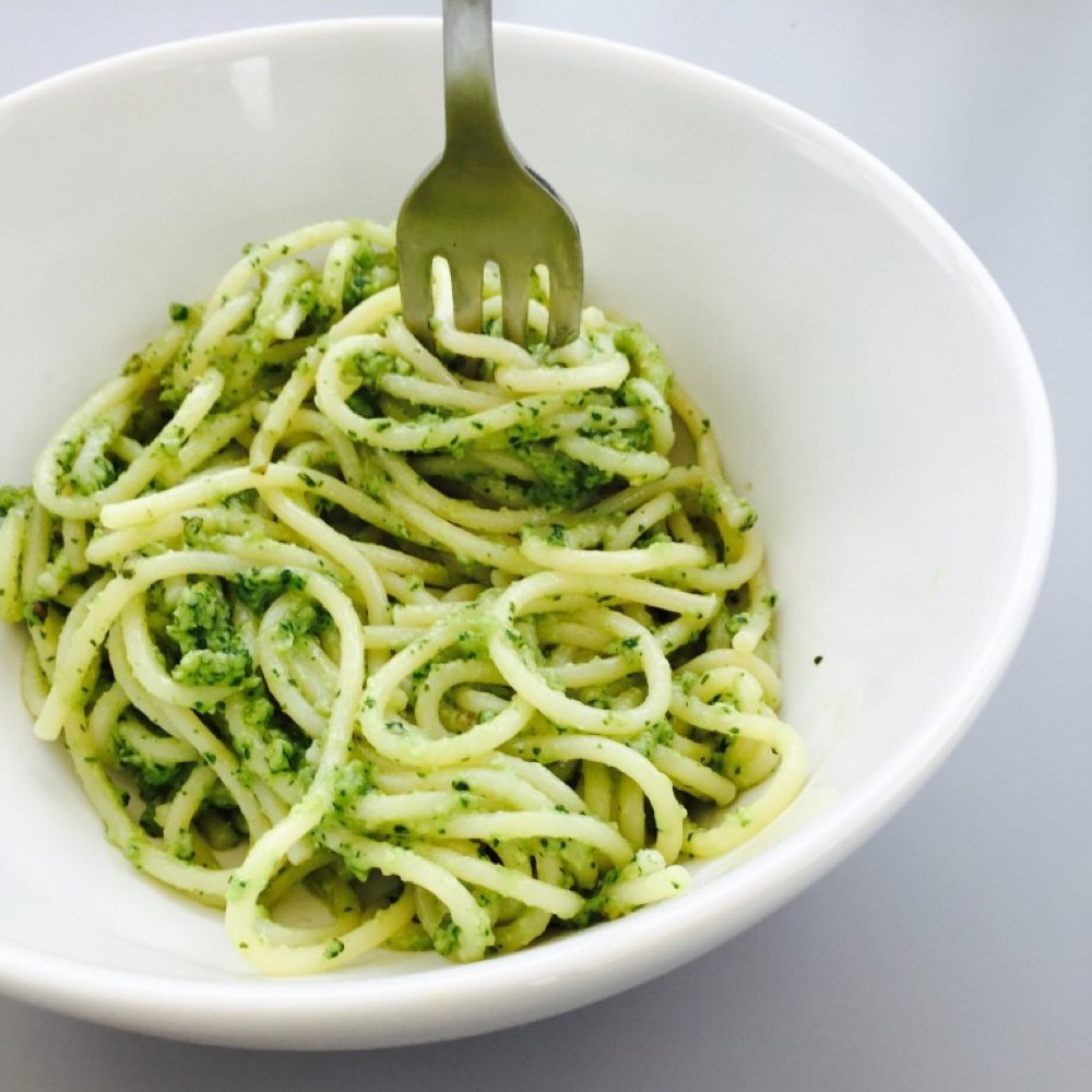 white bowl filled with freshly cooked spaghetti tossed with freshly made basil pesto