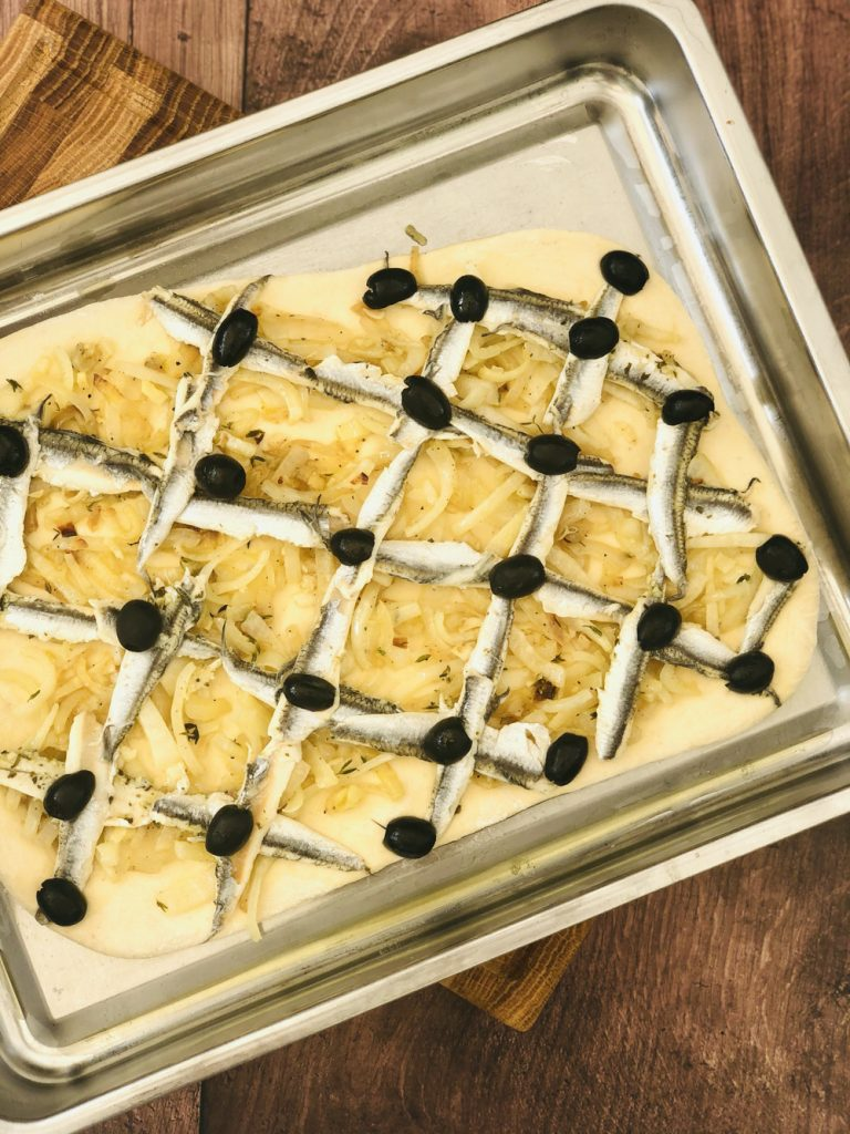 pissaladiere dough topped with onions and anchovy fillets laid in a criss cross diamond pattern across the dough, black olives on each cross