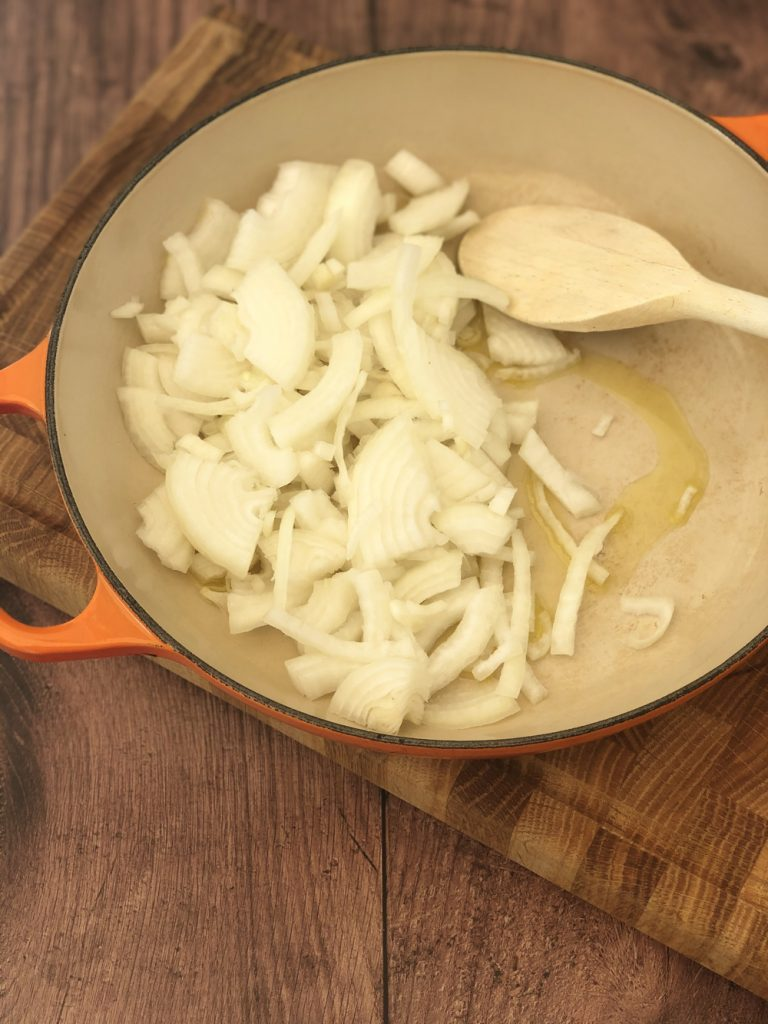 chopped onions frying in olive oil in a skillet pan