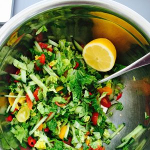stainless steel bowl filled with homemade spicy salad with coriander and chillies, lemon wedge on the side