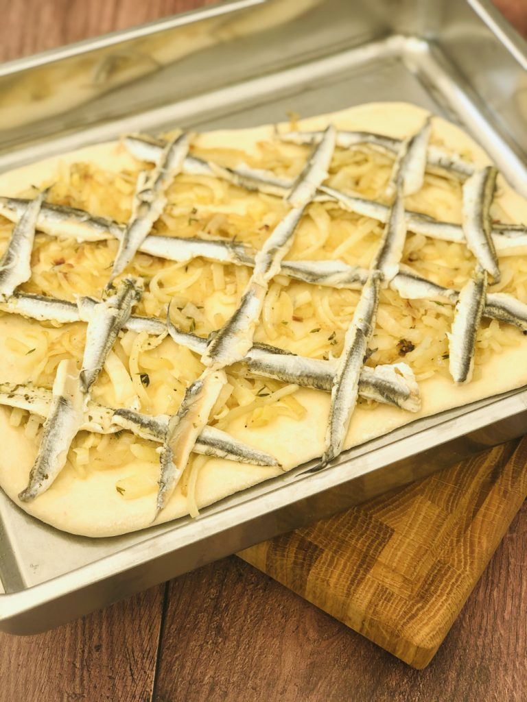 pissaladiere dough topped with onions and anchovy fillets laid in a criss cross diamond pattern across the dough