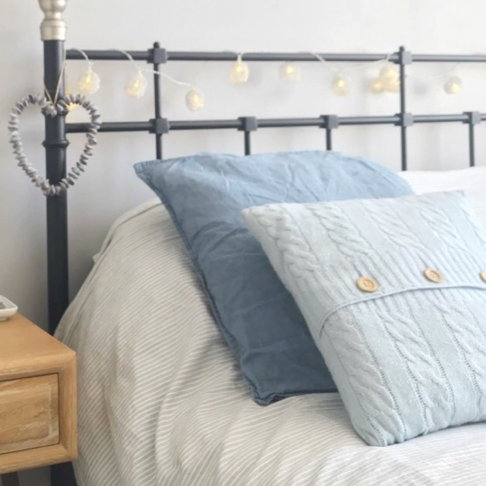 cast iron bed with grey striped bedding and plump pillows