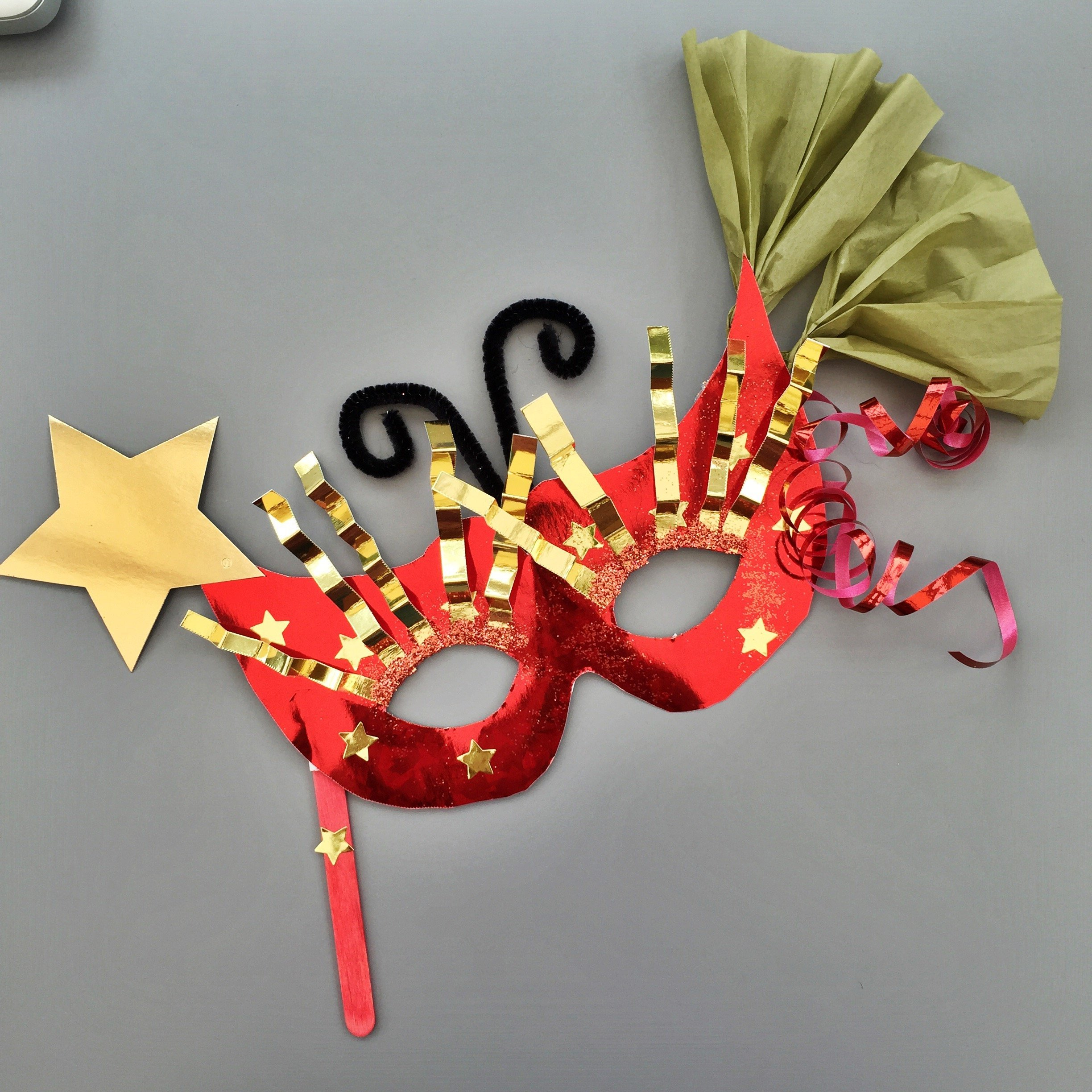 homemade kids carnival mask in red and gold decorated with stars, tissue paper fans, curly ribbon and gold eyelashes