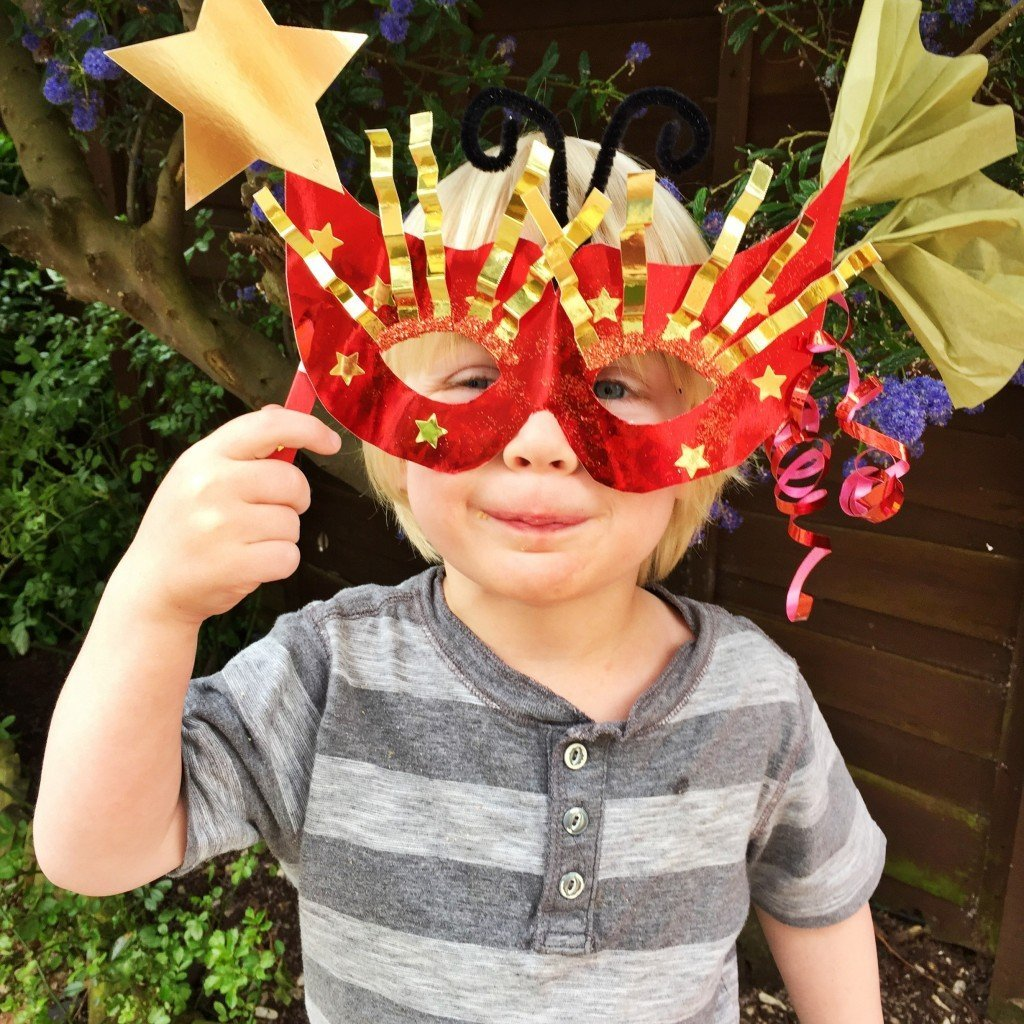 preschool boy wearing a homemade crafted carnival mask - made from red shiny card with metallic gold star decorations and ribbons.