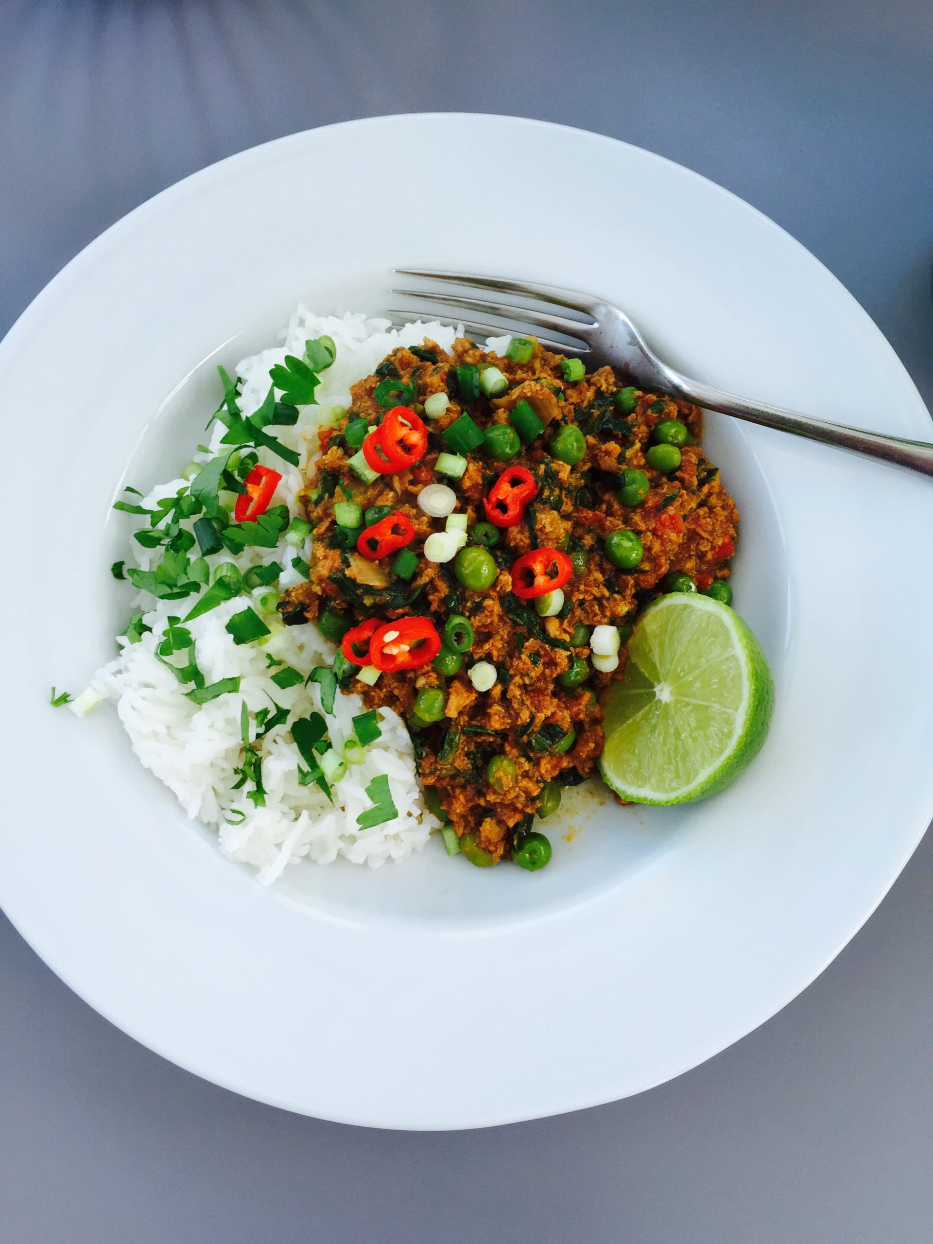 homemade slow cooker turkey keema curry served with plain boiled rice, scattered with chopped coriander and sliced red chillies, lime wedge alongside. Curry served on a white plate sat on a grey table.