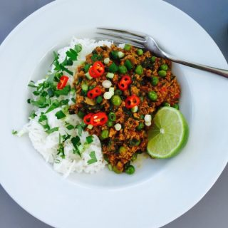 Turkey keema with white rice, scattered with red chillies, spring onions and coriander with a wedge of lime all on a white plate