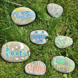 pebbles decorated with the names of herbs to be used as garden plant markers.