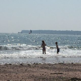 kids playing in the waves on the beach at Paington in Devon