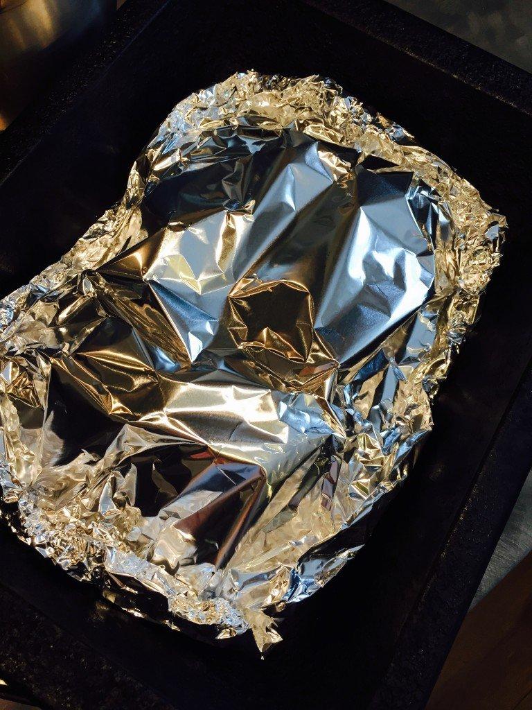 salmon fillets in foil parcel on a baking tray
