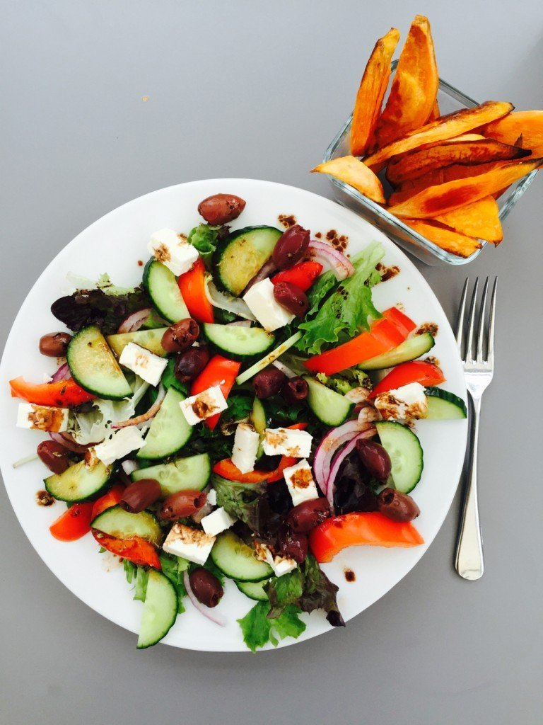 white plate filled with homemade greek salad and a side of sweet potato wedges