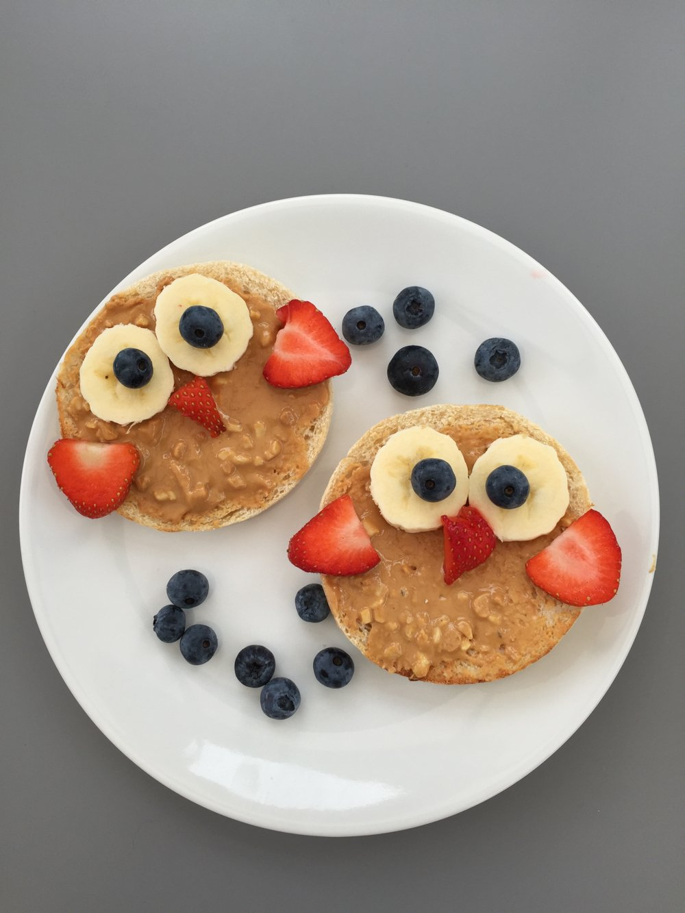 White Plate With Toasted Muffins Topped Sliced Bananas Strawberries And Blueberries To Create An The Cutest Looking Kids Breakfast