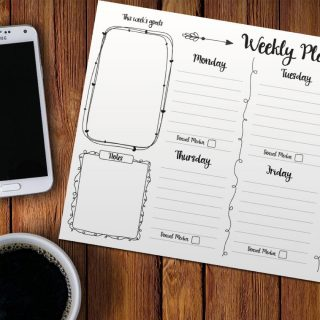 Black and white printed weekly planner on wooden table with black coffee in a white cup and a white samsung mobile phone