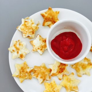 white plate with french toast stars and a small pot of tomato ketchup dip.