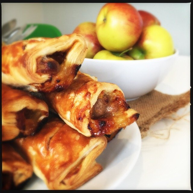 plate piled high with homemade sausage rolls with chutney and cheese - bowl of apples in the background