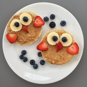 white plate with toasted muffins topped with sliced bananas, strawberries and blueberries to create an owl face
