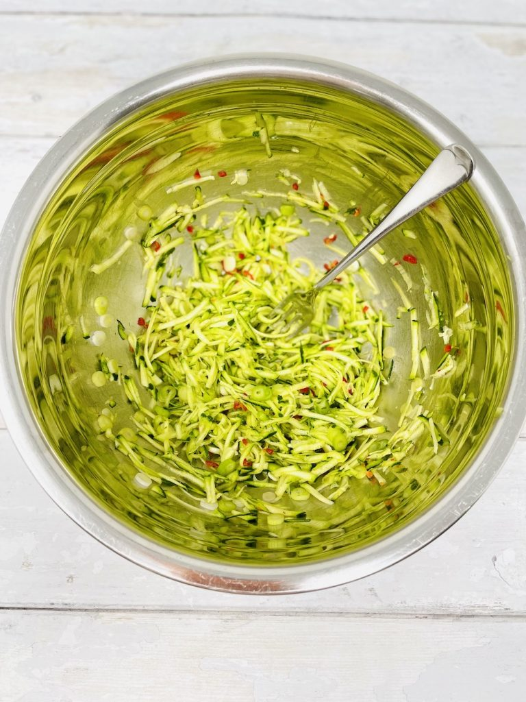 mingled together grated courgette, thinly sliced spring onions and finely chopped red chilli in a stainless steel mixing bowl