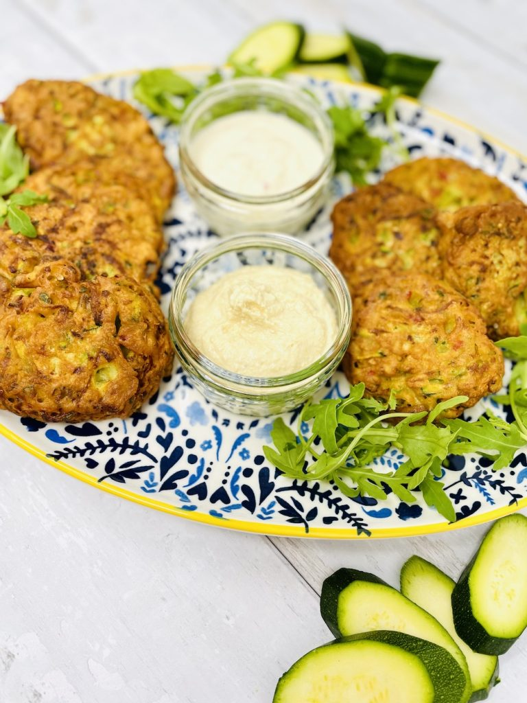 courgette fritters on a platter with chilli lime mayonnaise and hummus for dipping