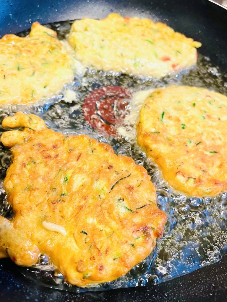 courgette fritters frying in sunflower oil in a frying pan