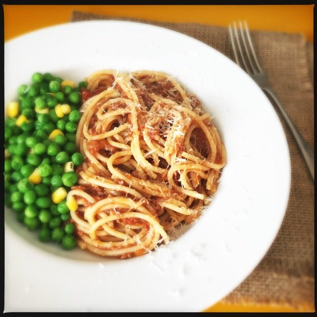 slow cooker spaghetti bolognese served with peas and corn