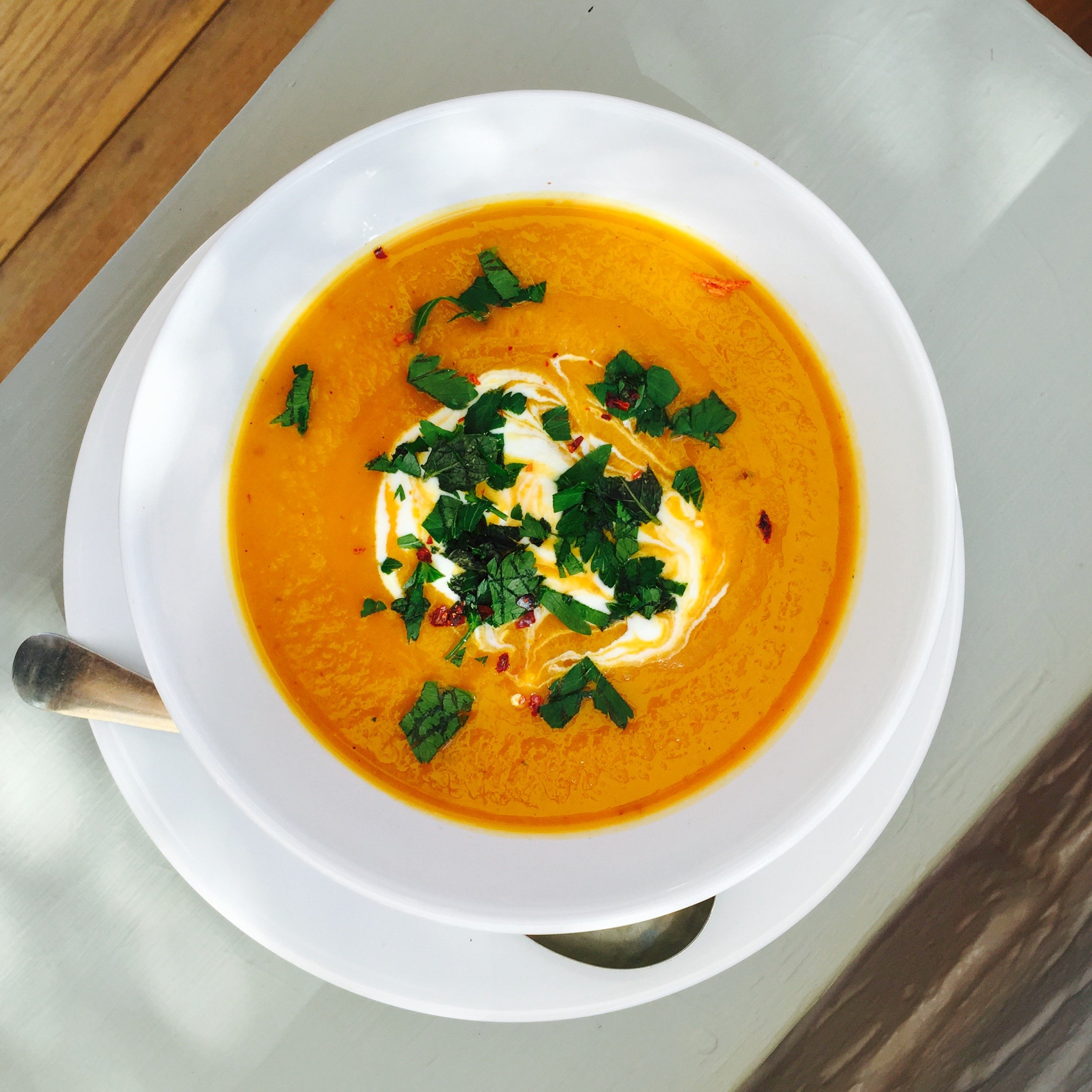 bowlful of moroccan roast vegetable soup with soured cream and herbs