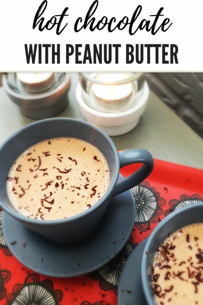 "homemade peanut butter hot chocolate with dark chocolate shavings on top. Served in little dusky blue cups with matching saucers on a red tray with black flowers. Two candles are flickering next to the tray.  Text overlay ""hot chocolate with peanut butter"""