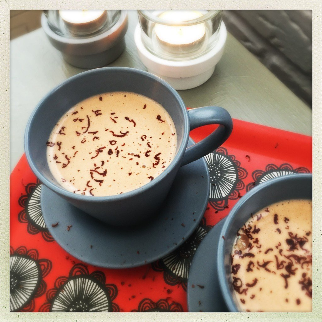 homemade peanut butter hot chocolate with chocolate sprinkles on top on a red flowery tray