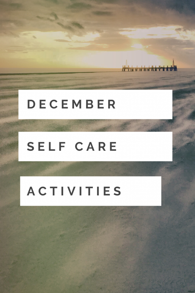 """beautiful wintery beach - sand is wind swept and blowing down the beach, the sun is low and the light is glowing and cold - pier in the distance. Text overlay """"December self care activities"""""""