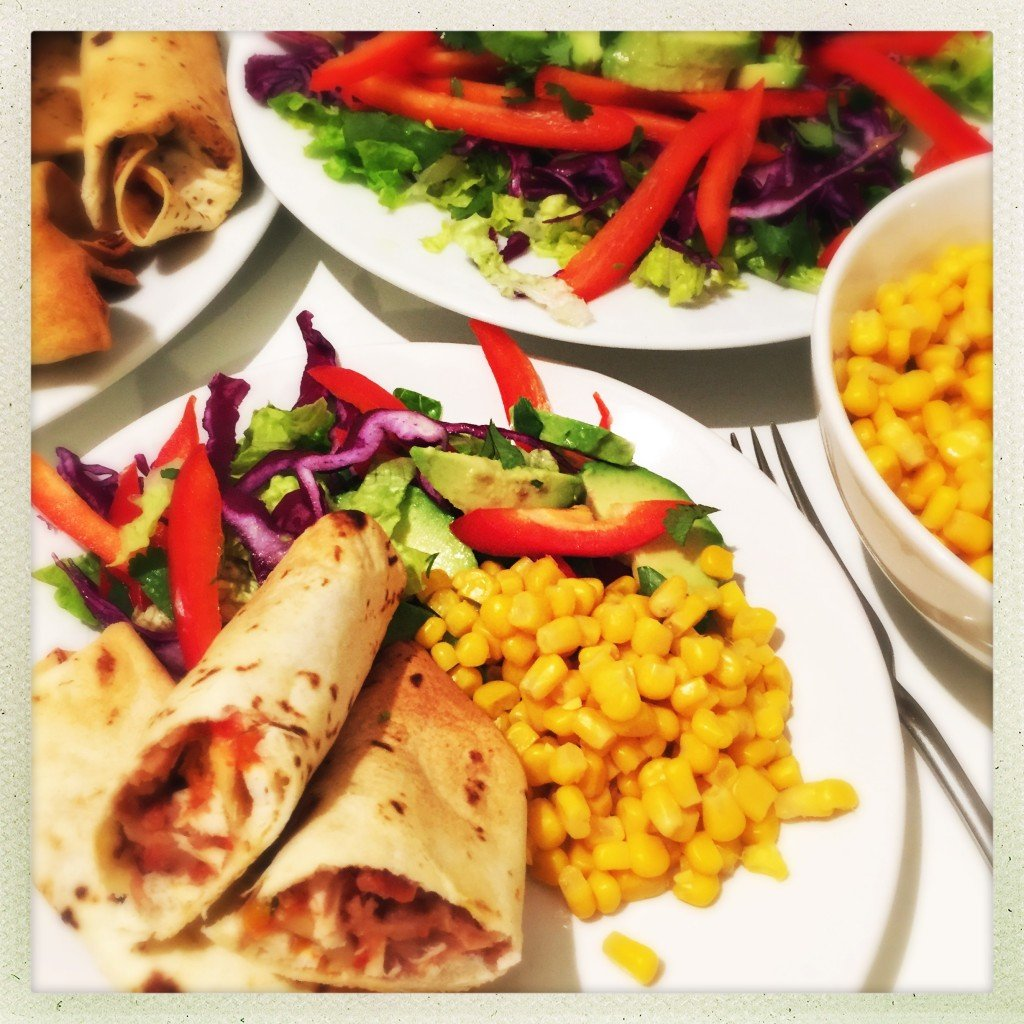 white plate with oven baked chicken chimichangas and pile of salad and sweetcorn, mixed salad in the background and white bowl of sweetcorn to the side