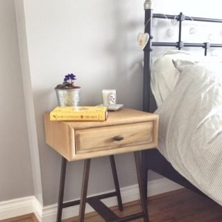 Loaf wooden bedside table next to IKEA black iron bedstead with grey and white striped cotton bedding. Bedside table has a silver pot with purple flowering plant in it and Diptyque candle alongside the book Great Western Beach